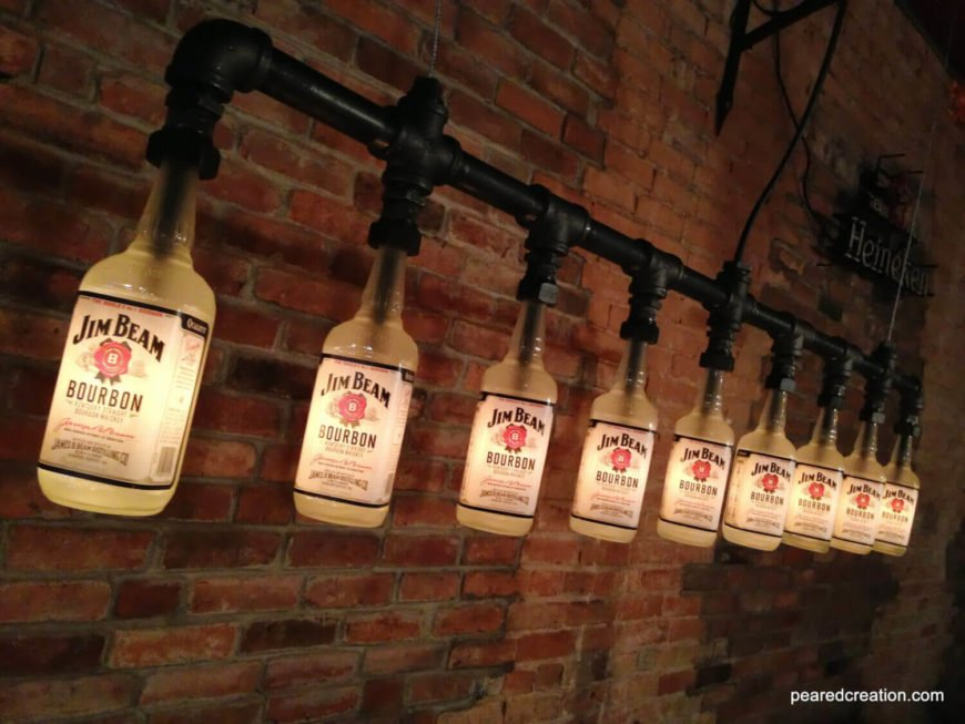 """This lengthy industrial chandelier re-purposes empty Jim Beam Bourbon bottles and was featured on the """"Man Cave"""" show. The light gives off a warm ambient glow using low wattage bulbs. The light fixture can be customized with different bottles, so you can feature your favorite brand!"""