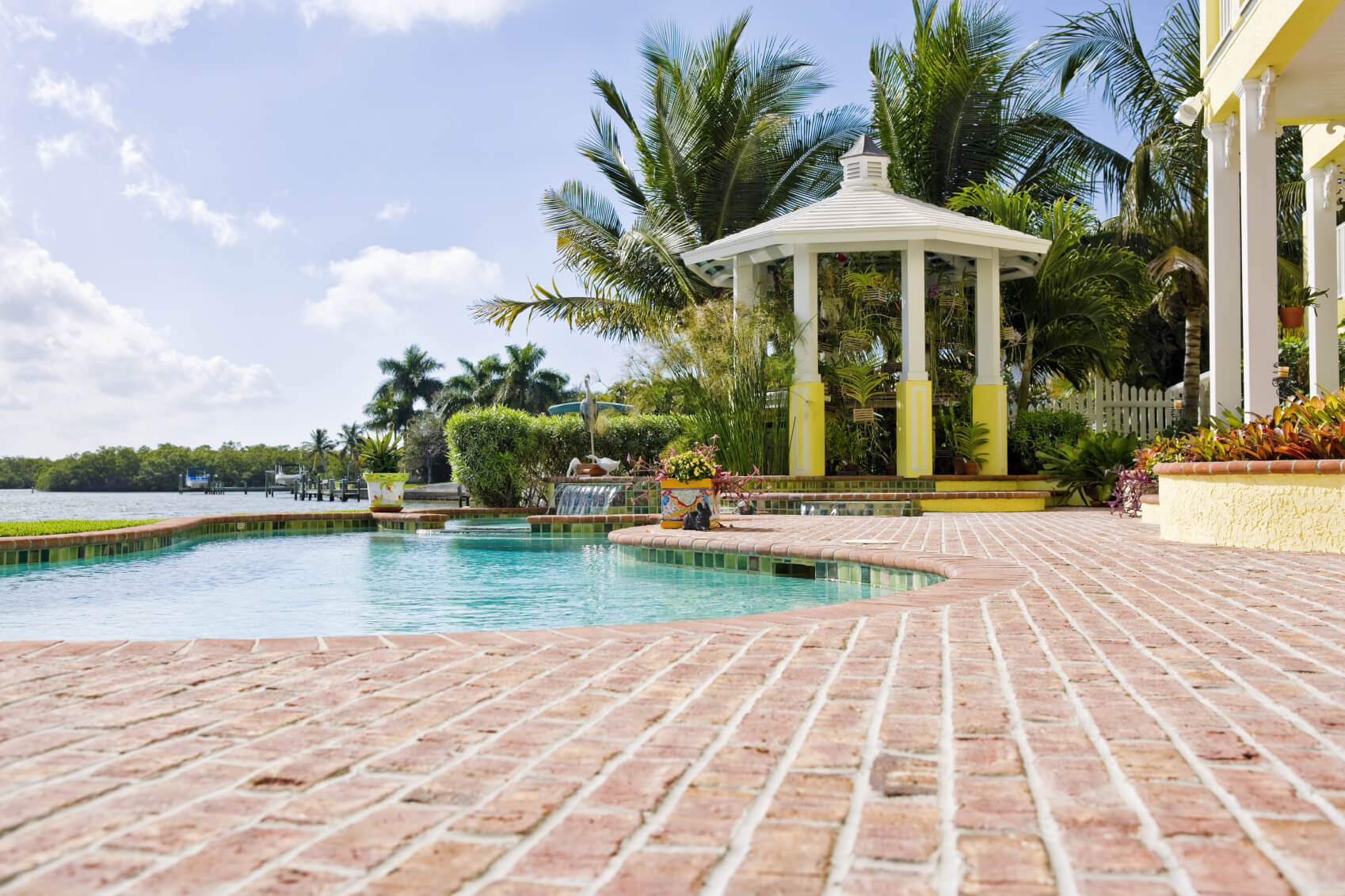 A gazebo can act as a transition between two different areas in your yard. Here it acts as a barrier to the densely wooded area on the other side of the pool.