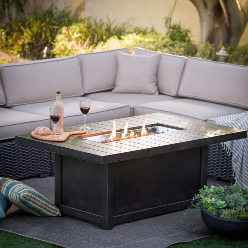 This high end coffee table with a firepit center feature can contribute to your backyard's atmosphere by providing heat and light, all while giving your guests great table space. This is a stunning centerpiece to any outdoor gathering area.