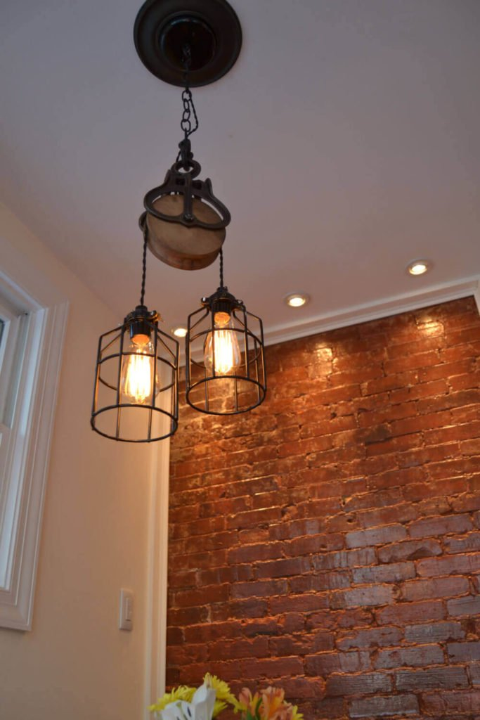 This lovely light is made using an antique barn pulley and features Edison light bulbs and removable cages on the lights. Using the pulley, the lights may be adjusted to the desired length.