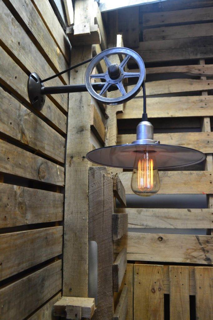 This unique wall light features an Edison bulb on a vintage cloth-covered cord draped over a vintage metal pulley. The light has a simple shade over the base of the bulb.