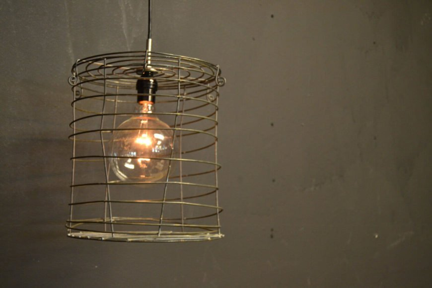 This flexible hanging light is encaged within a rustic, seemingly flimsy wire cage. The light features an Edison bulb and hangs from a simple black pendant cord, which is a standard 3 feet long.