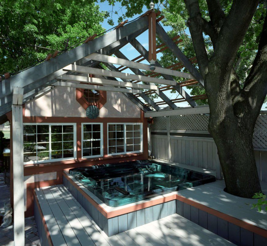 This hot tub has been integrated into the porch and deck and sits under a great gazebo. This provides additional shade on hot days and unites the hot tub area with the rest of the house.