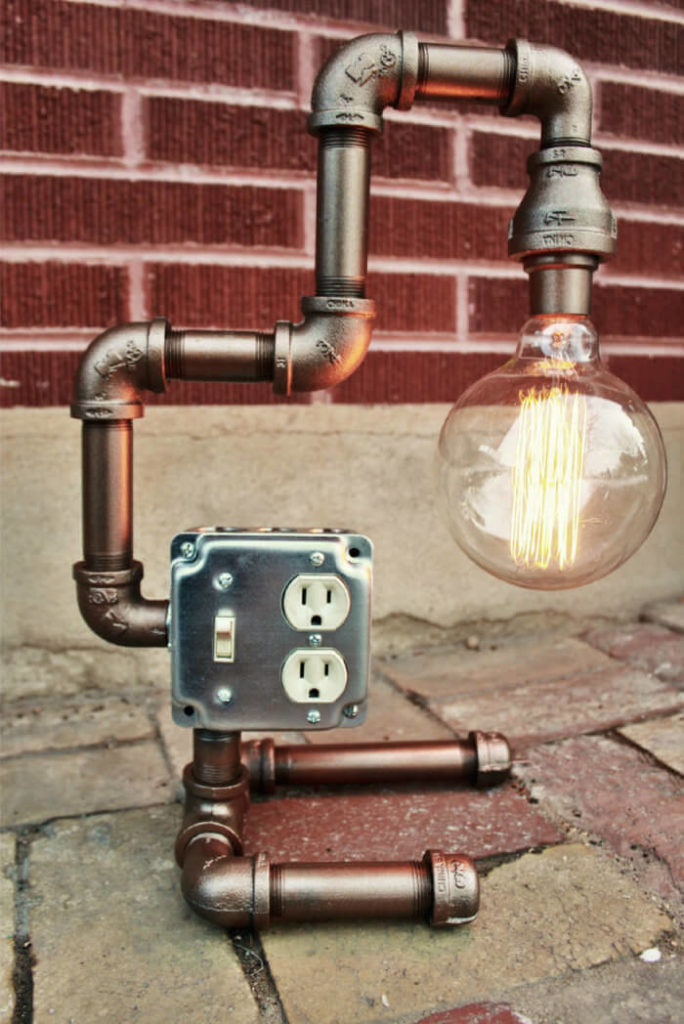 This lovely industrial pipe table lamp is bronze and features an Edison style light bulb. The piece is made with heavy industrial pipes, and may be used as a table lamp or as a wall lamp.