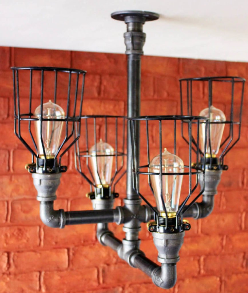 This lovely industrial chandelier has four twisted pipes fitted with caged Edison light bulbs. This piece works perfectly as a chandelier, dining room light, or bedroom light. The light is flush mounted to the ceiling.