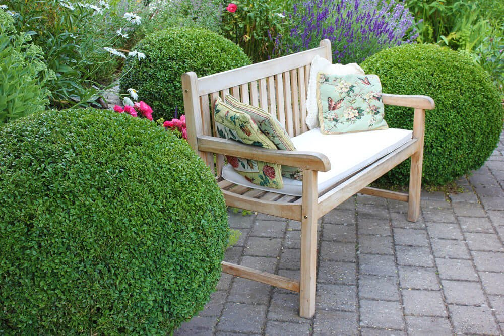 A wooden garden bench cushioned with floral throw pillows placed in between green topiary and in front of the nicely blooming pink flowers.
