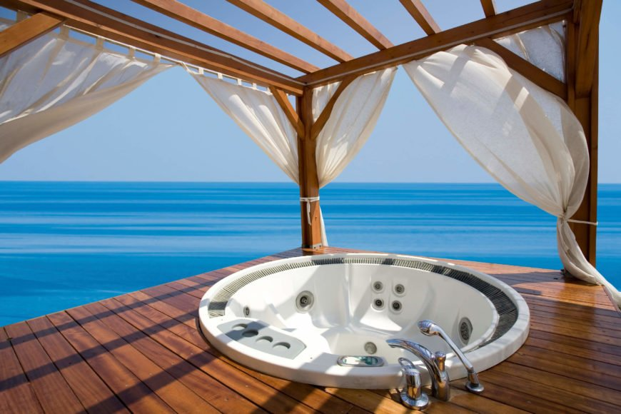 This gazebo and deck on the water is equipped with a hot tub as well as curtains. Curtains can be used as decoration or to increase privacy.