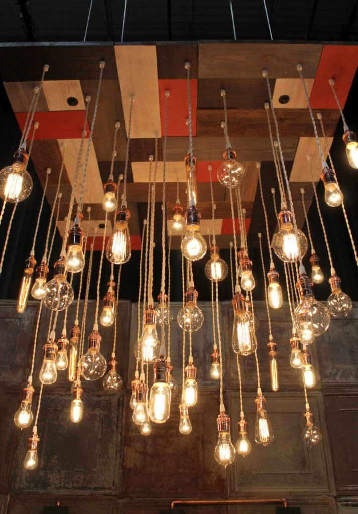 The mosaic wood base of this chandelier is made from reclaimed pine wood from New York, and is stained white, gray, brown, and red. The light has a total of 60 pendant lights fitted with copper hardware and copper trim. The light is available for hard wiring only.
