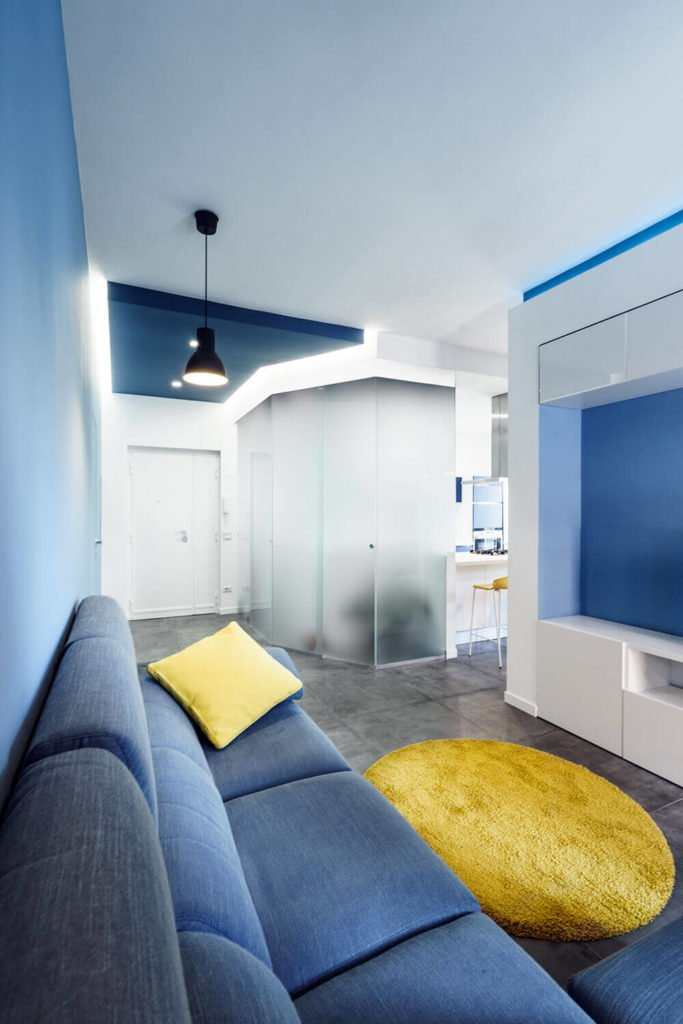 """As seen in the top featured image, the central open space of this apartment is awash in deep blue tones, while a sprinkling of yellow makes for stunning contrast. At center, we can see the frosted glass """"prism."""""""