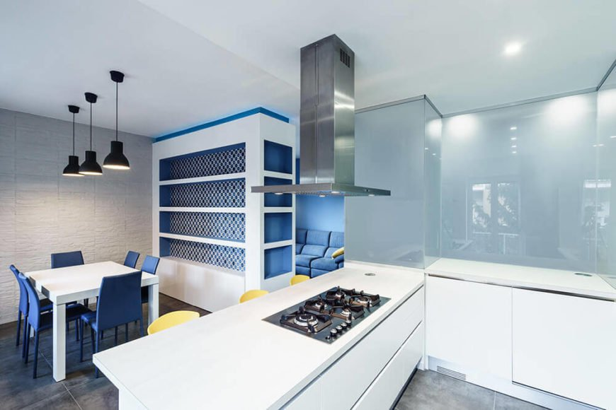 The kitchen is bursting with brightness, thanks to sleek, minimalist white cabinetry and countertops. The open layout means that the lengthy countertop doubles as an impromptu dining space.