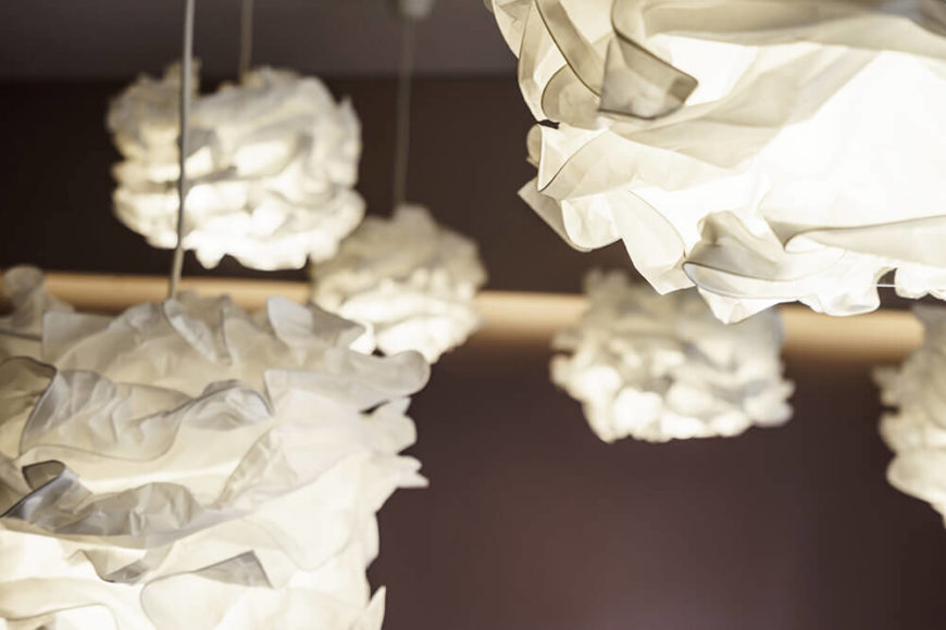 Here's a closer look at the unique lighting scheme in the primary bedroom. Carefully folded white paper materials create the illusion of clouds hanging over the room.