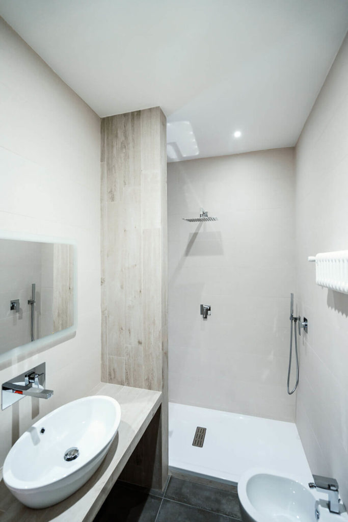 In the bathroom itself, we see the light natural wood accents adorning the minimalist space. Features like the white vessel sink and wall-mounted faucet increase the wow factor.