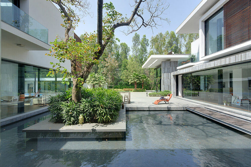 The courtyard features an intricate dance of natural and man made elements, most notably evoked in this wraparound reflection pool and the large tree at center. On both sides, rooms within the home can be seen through full height glass.