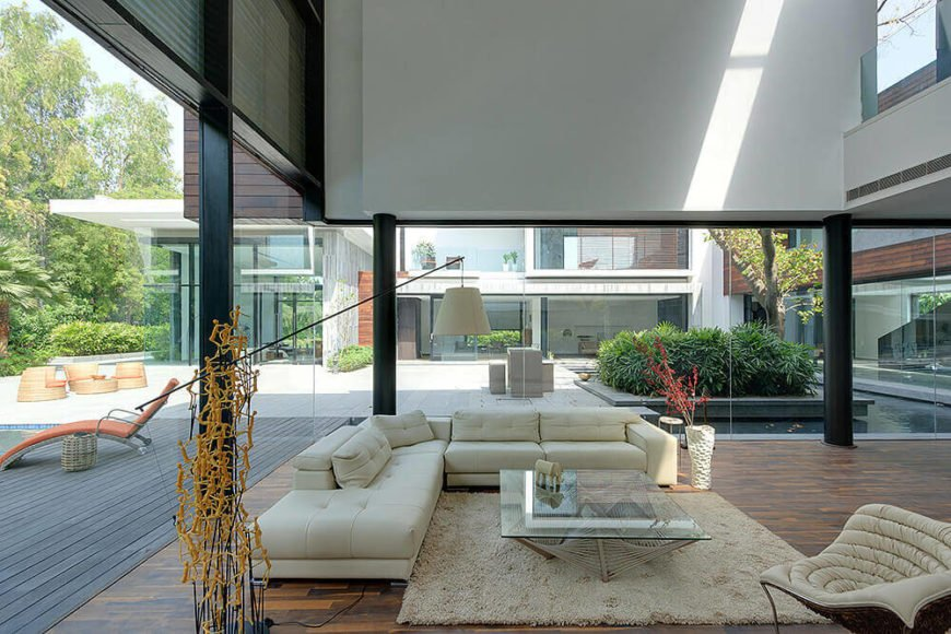 Now inside the home, we see the expansive views afforded within the living room, with glass wrapping entirely around. The courtyard can be seen clearly across the hardwood flooring.