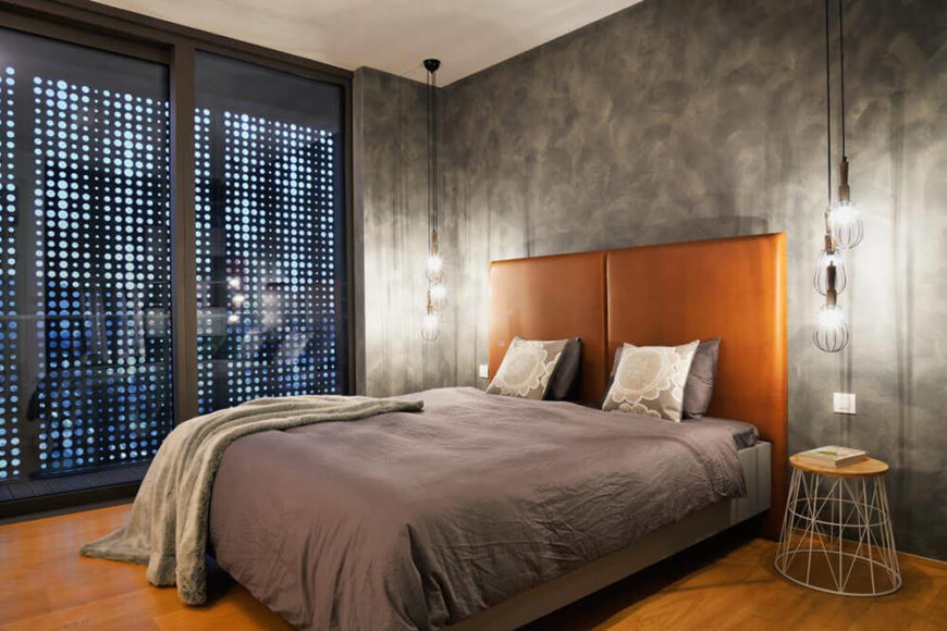 The primary bedroom is defined by a more industrial look, with concrete walls exposed an circular shade panels on the windows. The hazelnut headboard helps connect it to the rich hardwood flooring throughout the home.