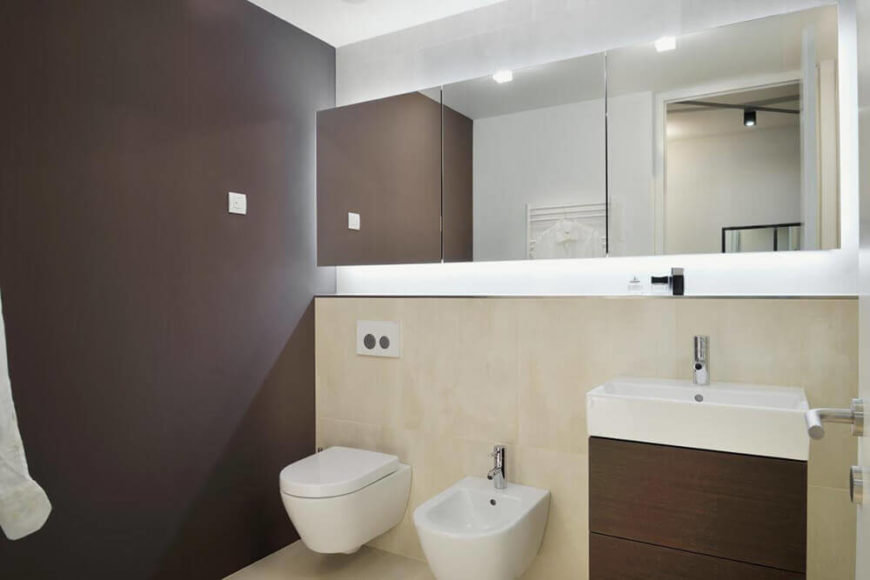 The primary bathroom is an exercise in tight elegance, with a floating, frameless mirror and compact vessel sink vanity standing out in a spartan space.