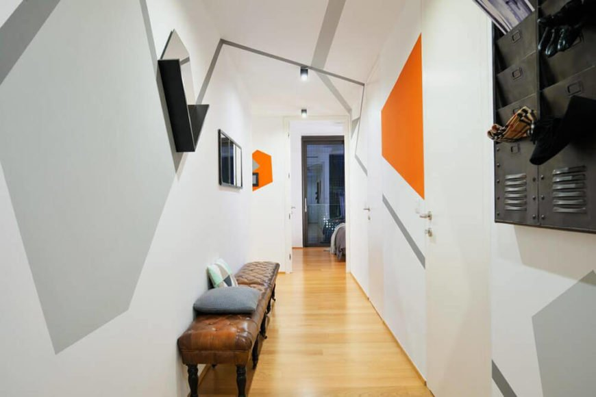 Here we see how the hallway appears when entering the home. The lengthy button tufted leather benches to the left add a bit of traditional style in contrast to the sharp, sleek home interior.