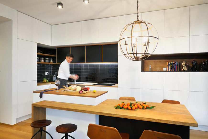 The kitchen boasts deep black subway tile backsplash as well as a rich natural wood shelf built into the wall. Touches like these add contrast and nuance to the modern space.