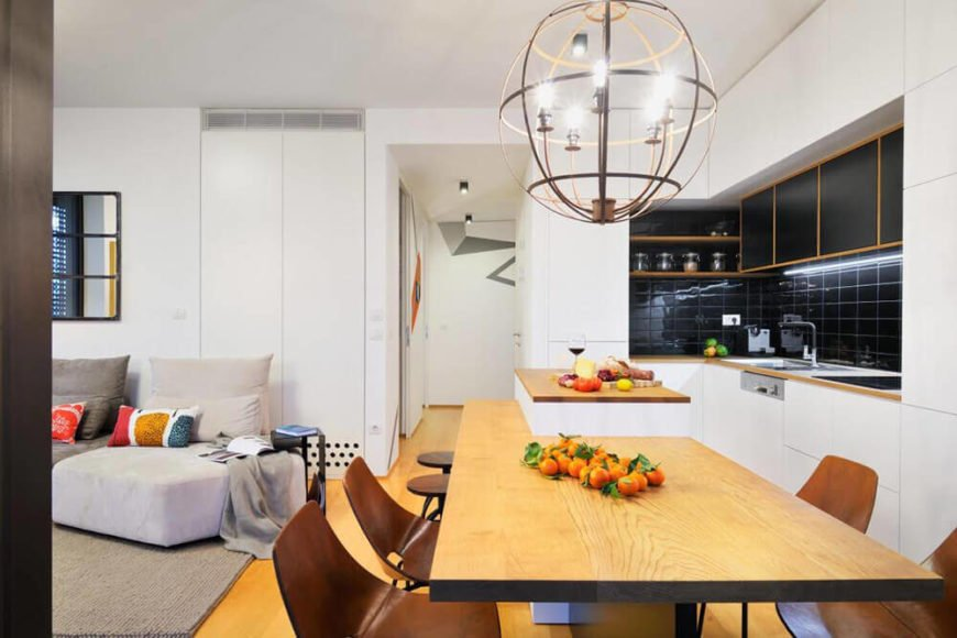 The lengthy kitchen island is a standout element of the space, providing both a working countertop and plenty of room for four diners. It also helps define the kitchen agains the living room area to the left.