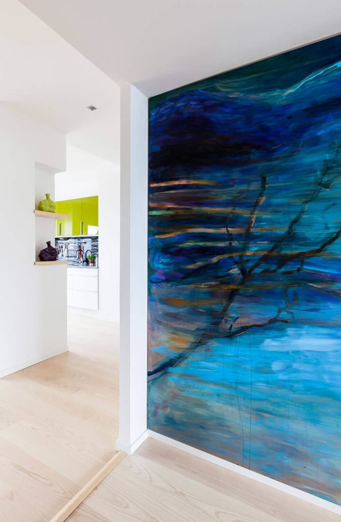 Moving toward the bedroom area, we see another bold artwork covering an entire wall here. This adds a surreal touch to the clean lines and minimalist style of the home.