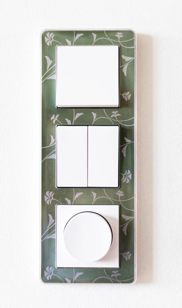 In a home with such detailed design, even the HVAC controls are a work of art. A floral print frames the sleek white dials.