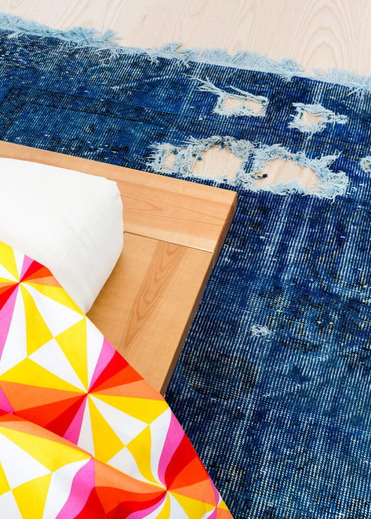 The bed platform appears to hover over the intentionally aged blue area rug, creating a slight rustic contrast to the space.