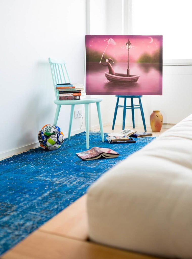 The minimalist design of the bedroom means that various objects are left to stand freely on the floor. Here a pair of brightly colored chairs creates a sort of art corner for the bedroom.