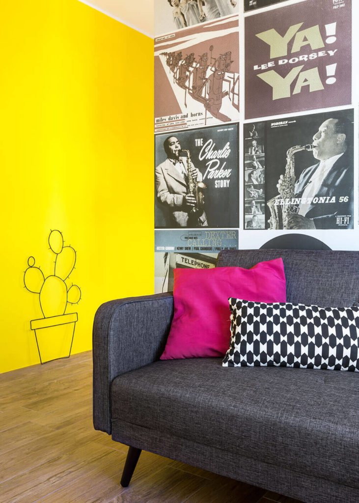 Here's a taste of that jazz legend wallpaper as well as the sleek, modern furnishings. Just to the left of the understated grey sofa we can see the metal cactus wall art.