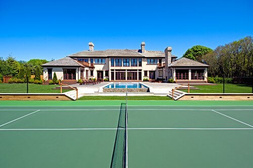 This lovely green tennis court matches well with the rest of the landscaping in this yard. The multiple shades of green build depth while staying connected and united.