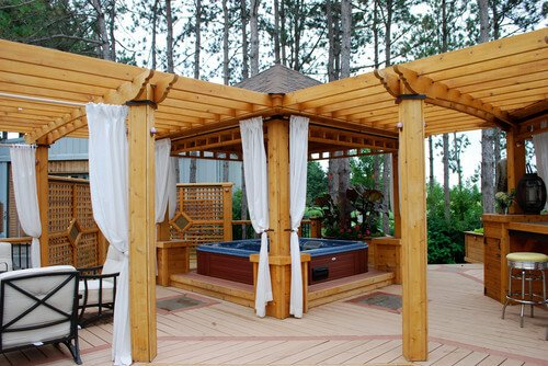 This gazebo has multiple different sections, one of which is dedicated to housing a hot tub. The portion housing the hot tub has a full roof to keep the space protected from the weather.