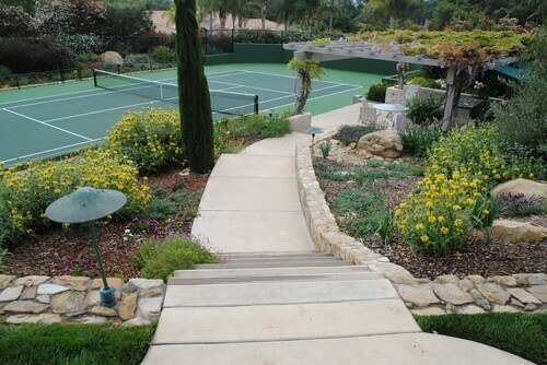 This tennis court is surrounded by fantastic greenery. Using gardens and hedges to accentuate your tennis court is a great idea for tying the sports area into your landscaping.