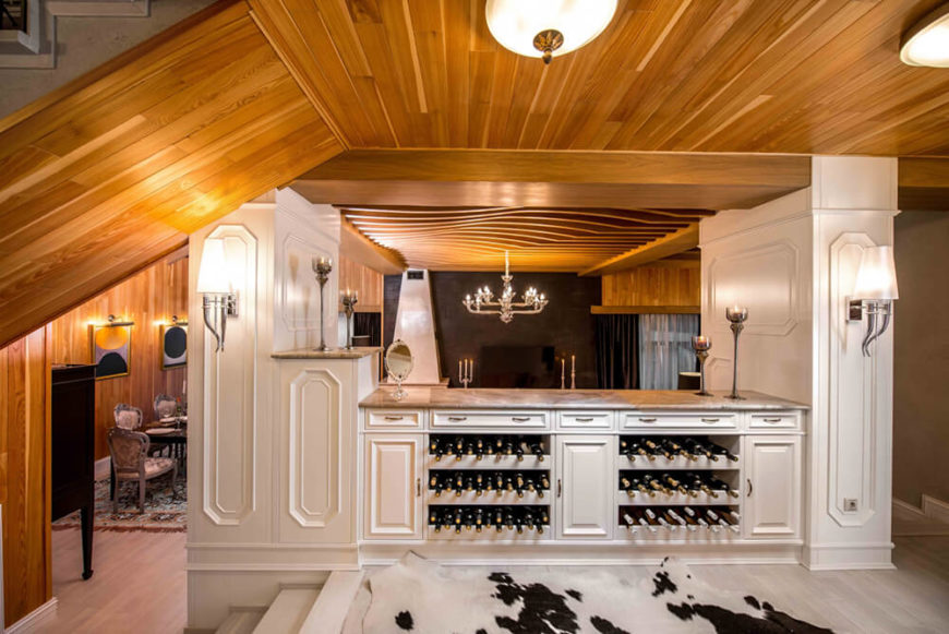 Moving up to the kitchen space, we see this unique island design with a built-in wine rack and marble countertops. A pair of elegant sconces glow over the light hardwood flooring.