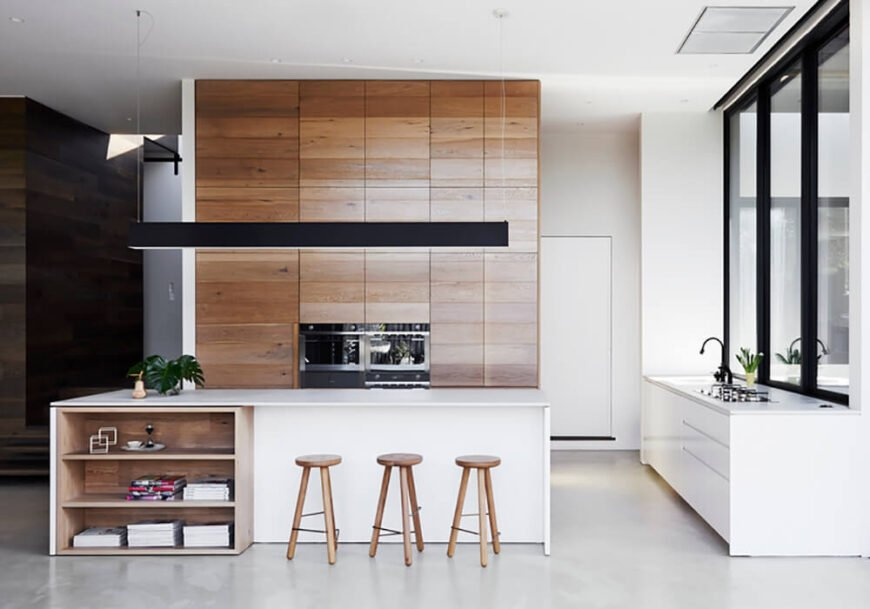 The kitchen features a large white island with unique natural wood shelving tucked beneath the countertop. Beyond, we see the floor to ceiling natural wood cabinetry, sleek and modern styled.