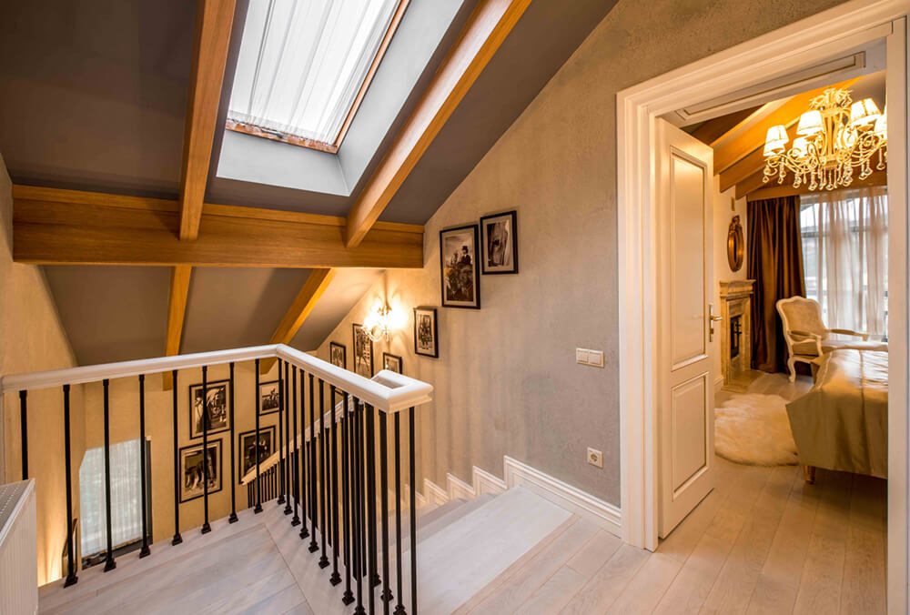 At the top of the stairs, we see how the rich natural wood exposed beams cross the entire home, unifying the layout and style.