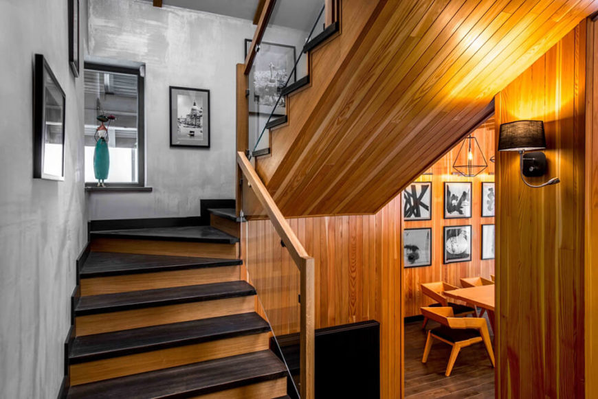 The staircase is wrapped with glass balustrades and the same rich wood as the walls of the lower floor. This creates a continuity as one moves up toward the private bedroom areas.
