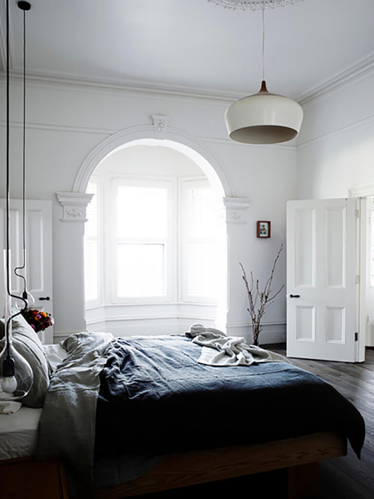 The primary bedroom continues the mixture of dark hardwood flooring and white walls, with a more ornate, old-fashioned look. Bedside light is provided by a pair of uniquely long pendant lights, wrapped in glass.