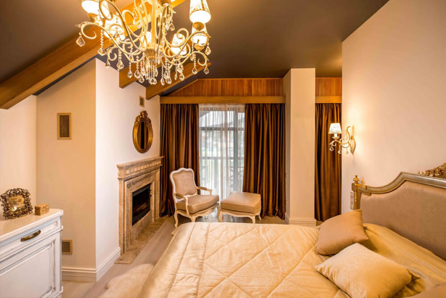 The primary bedroom features a large marble fireplace and relaxing area, all lit via chandelier and wall sconces. The detailed furniture glows before the large windows and rich wood accents.
