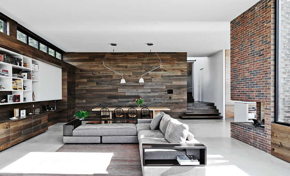 The large living room is bordered by rustic wood walls, a brick fireplace, and massive windows. The lengthy contemporary sofa anchors the vast room at center.