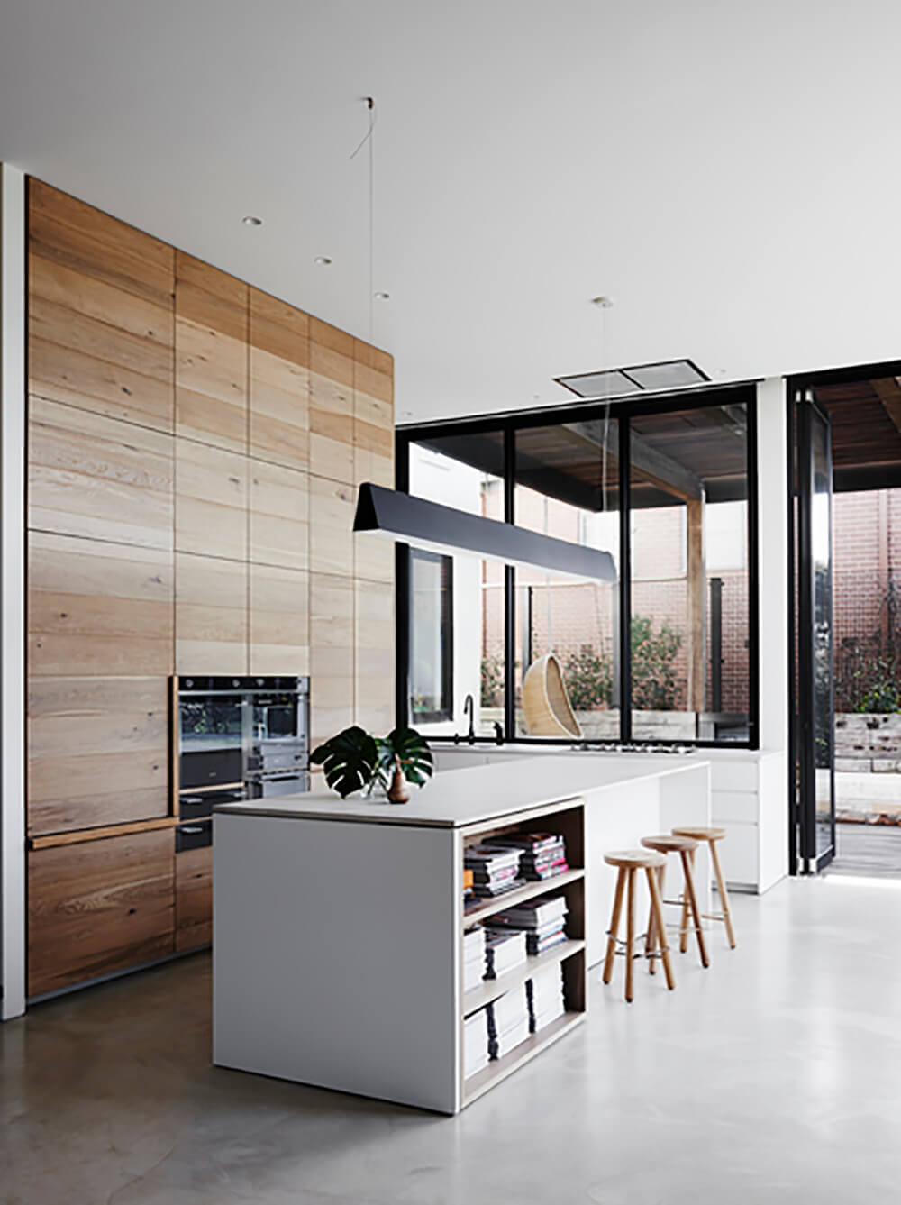 Just beyond the large windows, we can see the sprawling deck and walled-in backyard to the right. The glass panels retract to open the kitchen and living room up to this area.