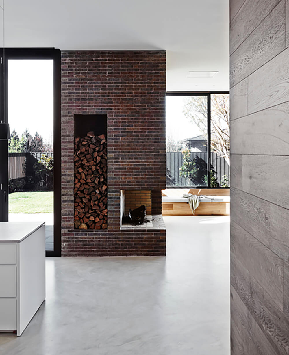 The fireplace is an integral part of the house, with its red brick construction anchoring the ultra-modern interior in a more timeless atmosphere. With built-in storage for firewood, it's as useful as it is beautiful.