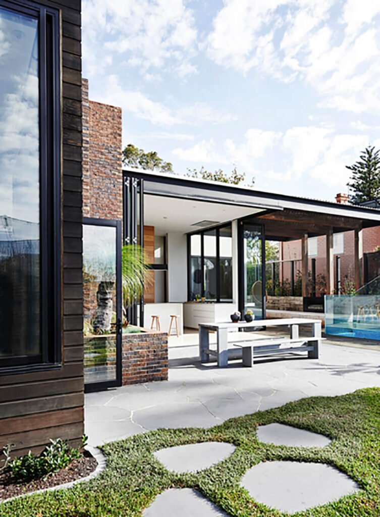 Moving outside, we see the fully integrated landscape and patio, combining many comforts of home with a sprawling lawn and balustrade-wrapped pool.