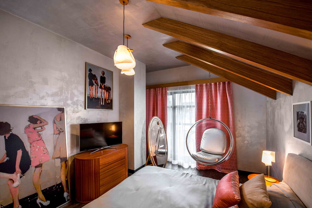 The bedroom also hosts a few idiosyncratic art pieces on the walls, in addition to a truly unique hanging sphere chair near the window. Touches like this add abundant personality to the modern space.