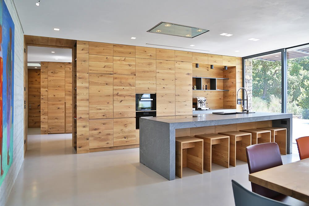 Dine-in kitchen with a gray island bar and natural wood cabinetry fitted with black double wall oven and floating shelves. It has smooth white flooring and floor to ceiling windows that bring plenty of natural light in.