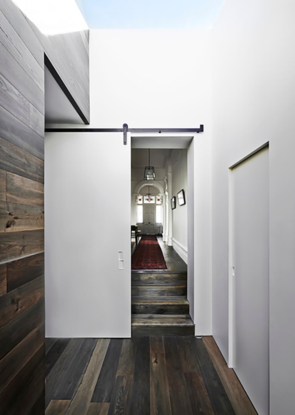 Moving down the hall toward the more private areas of the home, we see extensive natural wood flooring, contrasting with the white walls. A sliding door blocks off this space for social gatherings.