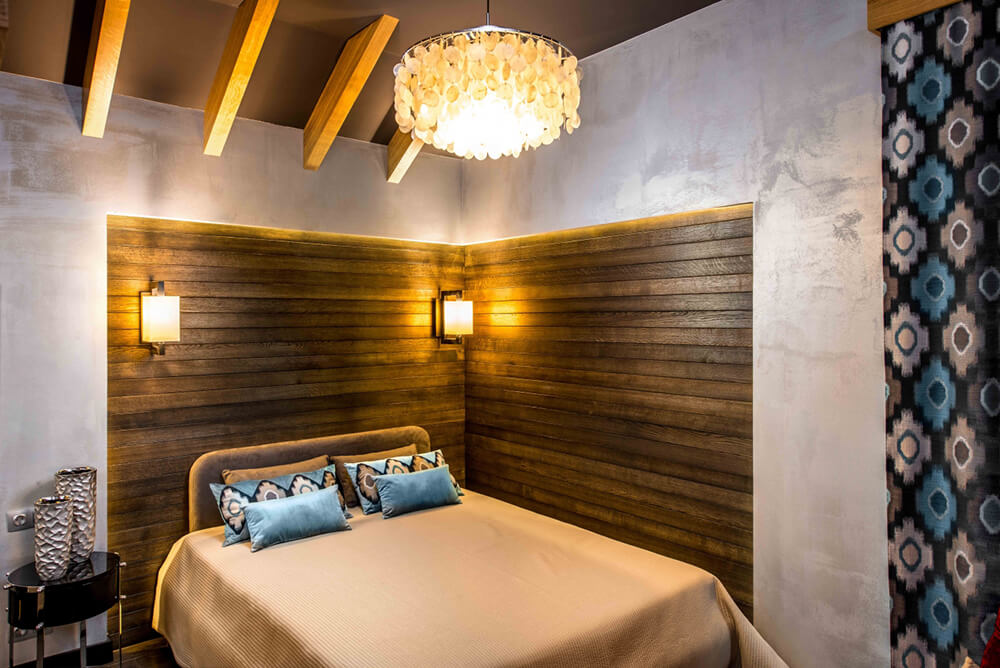 The second bedroom boasts rich wood paneling in the corner, contrasting the neutral tone of the concrete walls and bringing warmth into the room. An artful chandelier supplements the lighting of a pair of sharp angled sconces.