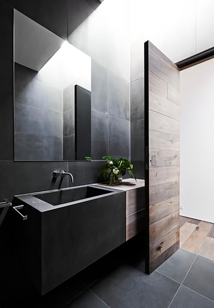 The bathroom is a very minimalist space, with dark large format tile flooring and a floating vanity in charcoal and natural wood. The room features a skylight for added natural light.