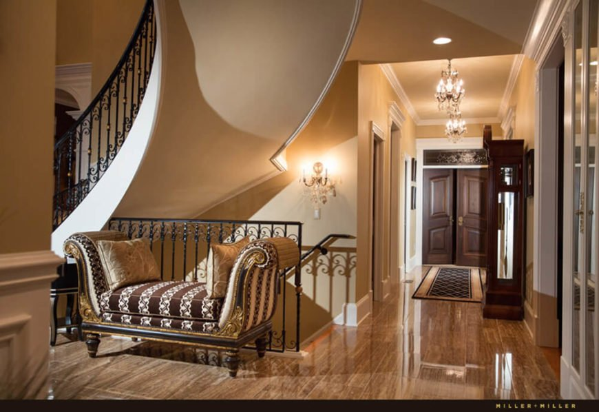 The rich flooring, detailed molding, and luxurious furniture appearing throughout the entry is a means of cementing an impression of the home right away.