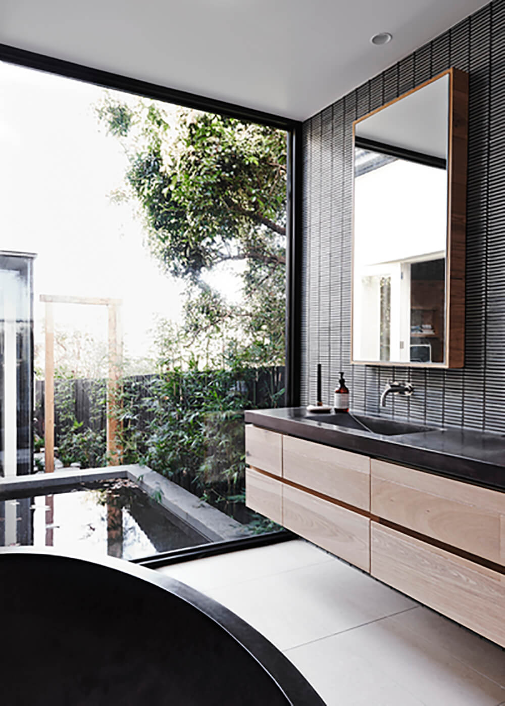 The primary bath features a massive window for expansive views over the landscape. With a floating vanity and large, oval shaped soaking tub, it's a comfortable and handsome space.