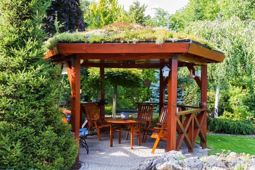 This unique gazebo has an interesting feature that draws the attention of anyone in the area. The roof is covered in plants and moss, blending the structure into the greenery around it.