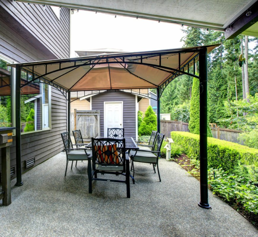 The slightly sloping canvas roof of this gazebo is just the right size for this somewhat narrow gravel patio. A dining table that sits six fits nicely under it with plenty of room between the edge and the chairs.